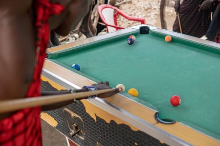 African masai men playing open air billiard pool in the village Sengare Sero at Masailand. Фото со стока