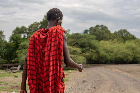 Maasai man in red traditional cloth walking near Lake Natron and Lengai volcano, Tanzania.