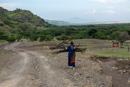 TANZANIA, EAST AFRICA - JANUARY 2020: Masai Woman in traditional clothes and weapons are walking in the savannah by the Gravel Road with Mountains on Background Editoriali