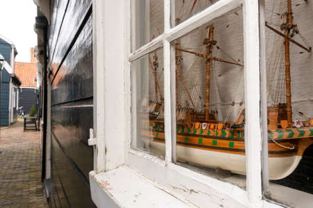 Close-up of the little marine white ship model from the wood on a windowsill in the Wooden Traditional House in Marken, Netherlands
