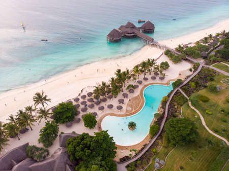 Top View on Beautiful thatch stilt house restaurant and Resort with Pool at Zanzibar Kendwa beach at evening time in Turquoise Water of Indian ocean