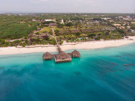 Top View on Beautiful thatch stilt house restaurant at Zanzibar Kendwa beach at evening time in Turquoise Water of Indian ocean