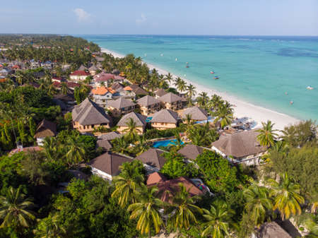 Aerial shot of a luxury hotel on a Beach first line with Palm Trees Garden at evening time in Paje village, Zanzibar, Tanzania