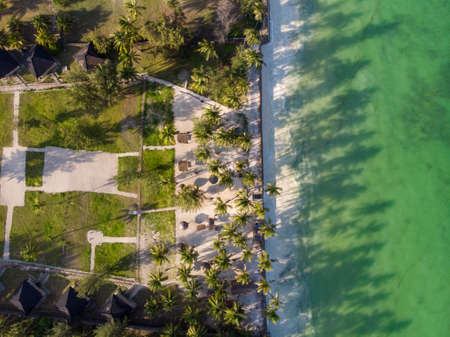 Aerial shot of a luxury hotel on a Beach first line with Palm Trees Drops their Shades on a High Tide Water of Indian Ocean at evening time in Paje village, Zanzibar, Tanzania