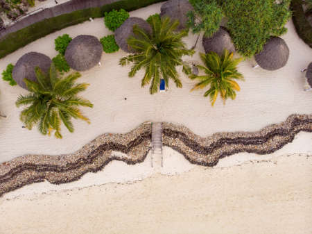 Top Aerial view of Thatched roofed beach umbrellas of luxury ocean view resort at the beautiful white sand ocean coast in Nungwi at Zanzibar island, Tanzania