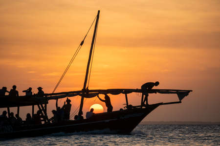 Dhow sailing during sunset in Zanzibar. Dhow is a wooden vessel with a sail, used to transport goods. Mostly used in Indian ocean