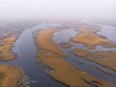 Aerial Shot of the Misty Autumn Floodplains of the Dnieper River with Reed islands in the river