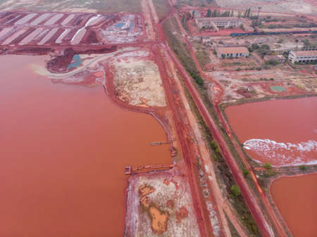 Aerial Bird eye Top View at Red Clay Pools With a Gateway Sluices Seethes: Spillway of a Clay Factory