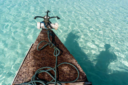 Bow side of Traditional Zanzibar Dhow boat with anchor and Rope at the Shallow Beach Water with Shade of Sailor