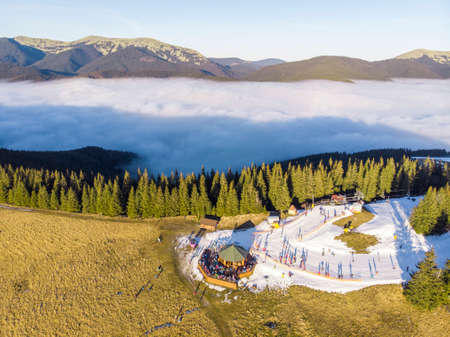 Aerial panorama of Bukovel Ski Resort mountain Dovha, Particularly covered with a Man-made Snow. Low clouds hang around the mountain and People on Skies and Snowdoards Are enjoying Sunset in Top View Panorama Restaurant.