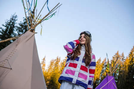 Portrait of Pretty Caucasian young woman Near Tipi or Wigwam in ski outfit and Winter Sports Mask on her Head. Portrait of cheerful blond woman at ski resort