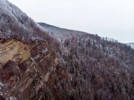 Wonderful landscapes of the Carpathian Mountains covered with snow at Cloudy Day in Ukraine near the village of Vyzhnytsia and River Cheremosh
