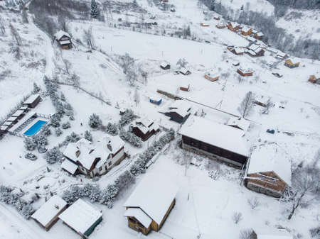 Aerial view of a Mountain Village with Hills Covered in Snow and Pine Forest in Winter. Yaremche, Ukraine. Flying over the snowy hills and wooden small houses. Countryside, fir tree. Drone view 版權商用圖片