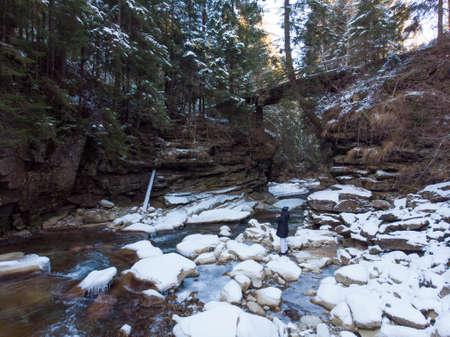Winter Frozen Stream Flowing Under the Small bridge in Natural Stone Arch in Deep Valley. Carpathians Mountains, Ukraine