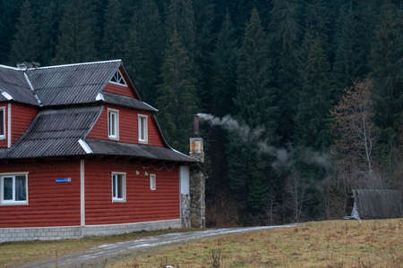 White smoke from the chimneys of Accurate Wooden houses in a mountain village in Autumn on a background of forest and mountains