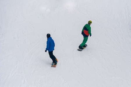 Two Snowboarders riding on White Snow Covered Slope top view