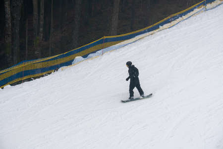 Snowboarder riding on White Snow Covered Slope top view