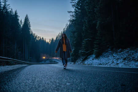 Beautiful Young Woman On the Dark Forest Road at Winter. Twilights, Car Lights on Background