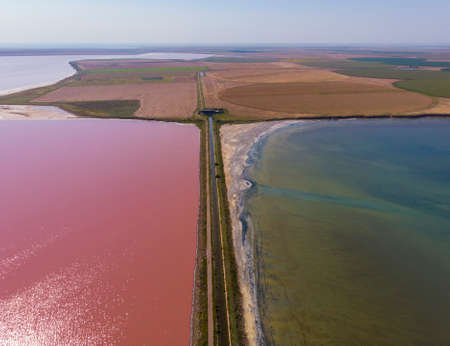 Aerial Drone Shot of a Dam with asphalt Road between Estuaries with Different color of Water. Pink Orange Lake and Green or Blue lake aside a road in Ukraine. Lake Sivash 版權商用圖片