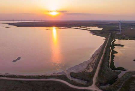 Aerial Drone Shot of colorful pink lake at sunset time with wind turbines farm on background. Cinematic landscape view picturesque margenta water in Ukraine, Kherson Oblast, lake Syvash