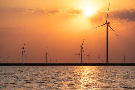 Silhouettes of wind turbines farm Behind the Lake at Sunset. 版權商用圖片
