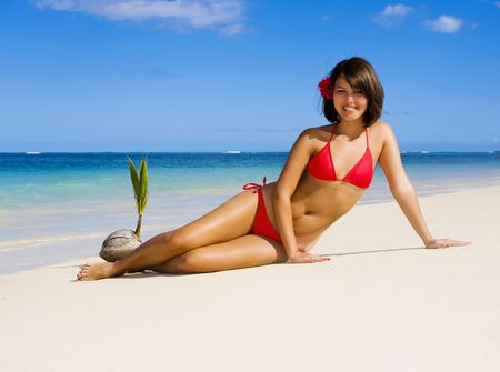 a beautiful young Polynesian girl in a red bikini on a Hawaii beach Stock Photo