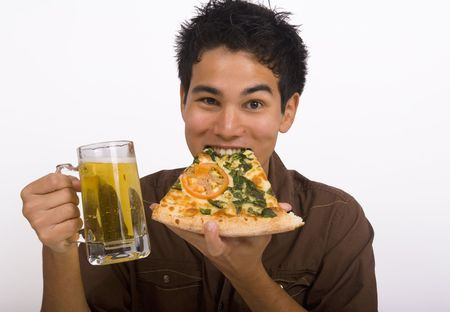 A young Asian American man enjoys a glass of beer and a slice of pizza