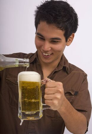 A young Asian American man enjoys a glass of beer Stock Photo - 4371094
