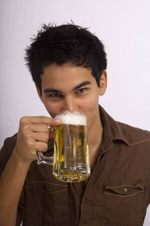 A young Asian American man enjoys a glass of beer Stock Photo - 4371093