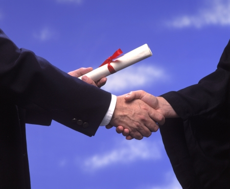 A diploma presented with a handshake and congratulations