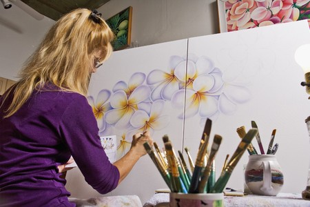 A female artist painting on canvas in her studio Stock Photo