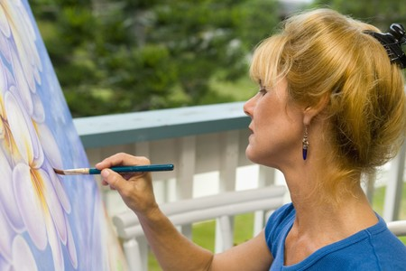 A female artist painting on canvas on her studio balcony Stock Photo