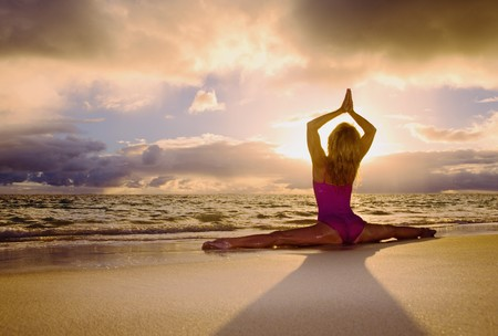 A fifty year old woman doing yoga and stretches on the beach photo