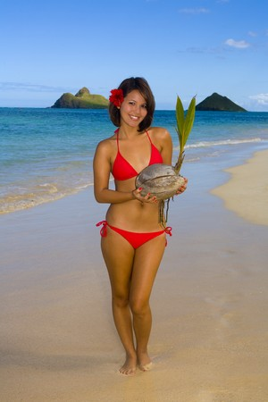 beautiful Polynesian girl in  bikini on a Hawaii beach with coconut photo