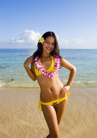 beautiful Polynesian woman in a yellow bikini smiling at a Hawaii beach