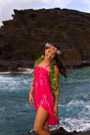 inlet bay: hawaiian girl with flowers on lava cliffs by the ocean Stock Photo