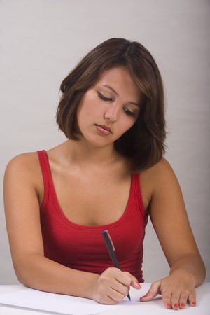 person writing: a beautiful young Asian-American woman writing a letter Stock Photo