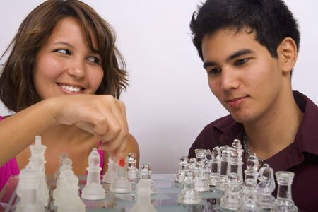 Two Asian American siblings playing a game of chess Imagens