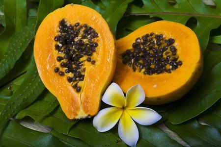 papaya flower: a fresh Hawaiian papaya cut in half with a plumeria flower