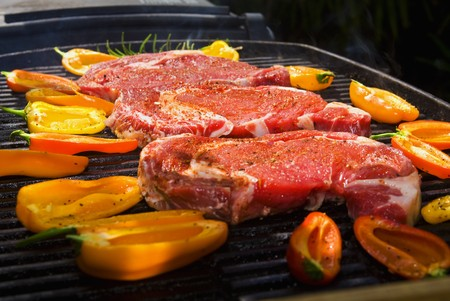 ribeye steaks cook on the bar-b-que grill with baby bell peppers Stock Photo