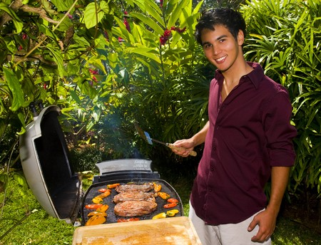 A young Asian American man grilling steaks in his yard photo