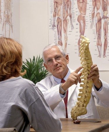 a chiropractor showing a patient a model of spine photo