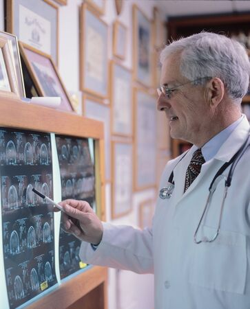 a neurosurgeon looks at brain scans in his office photo