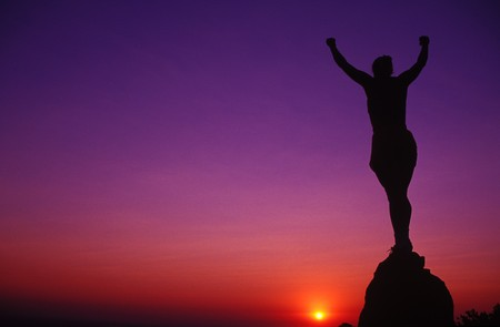 a woman silhouette holding her arms up in victory on a mountaintop photo