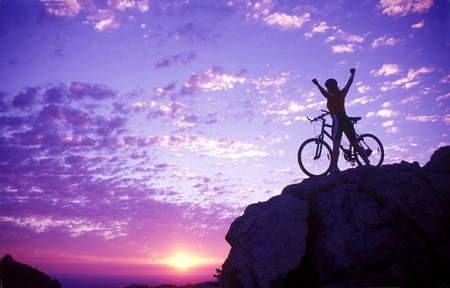 conquest: a woman on a bike holding her arms up in victory on a mountaintop