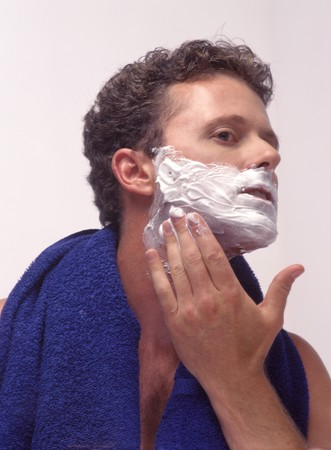 a young man shaving his face in the mirror
