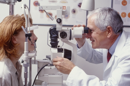 eye doctor: optometrist with patient, giving an eye examination Stock Photo