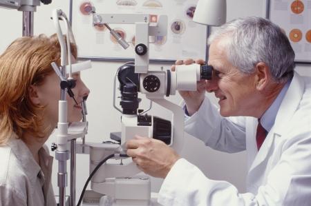 vision test: optometrista con paciente, dando un examen de los ojos