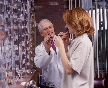 optometrist with patient, trying on new glasses photo