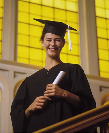 A university graduate in cap and gown with her diploma Imagens